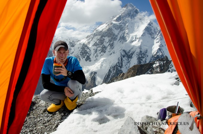 Nick drinking tea after setting up high camp II (6400m) with K2 visible in the background