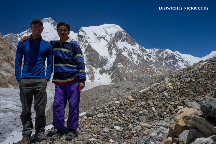 Nick Rice and Little Hussain in Gasherbrum Base Camp with Gasherbrum I's summit visible in the background