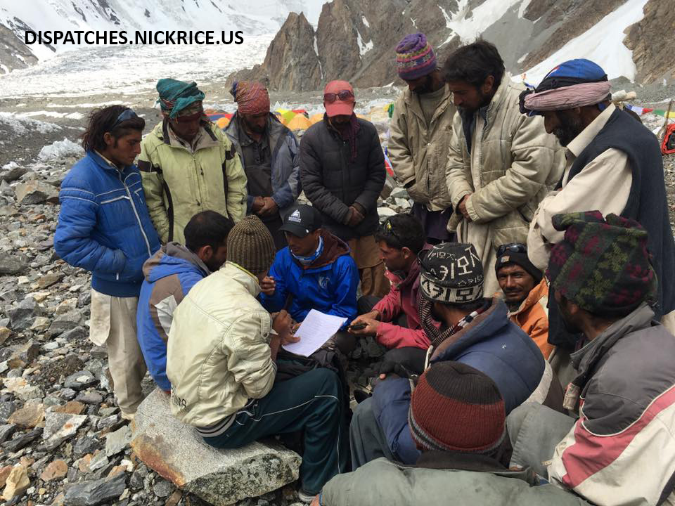 Porters gather around as payments are calculated in K2 Base Camp